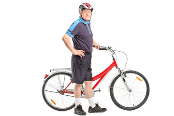 Active senior pushing a bicycle and posing