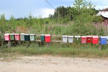 15 Briefkästen in verschiedenen Farben in der finnischen Provinz