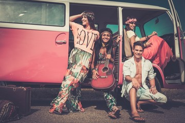 Multi-ethnic hippie friends with guitar on a road trip