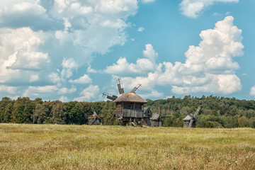 Old wooden windmills on the field.