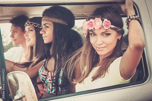 Multi-ethnic hippie friends in a minivan on a road trip - 68664021