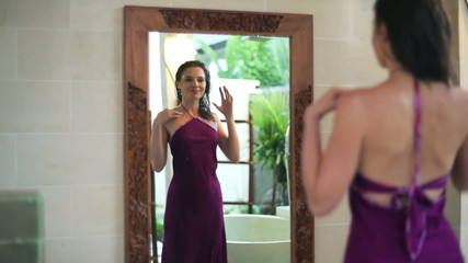 Beautiful woman looking at her appearance in the mirror