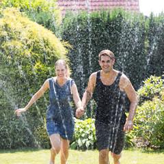 Paar läuft zusammen durch Wassersprenger