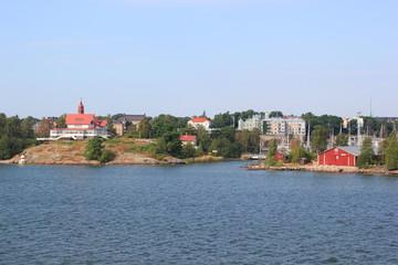 Rote Holzhäuser auf Schären vor dem Hafen von Helsinki