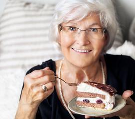 Seniorin genießt Sahnetorte