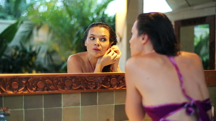 Beautiful woman put on earrings in front of the mirror