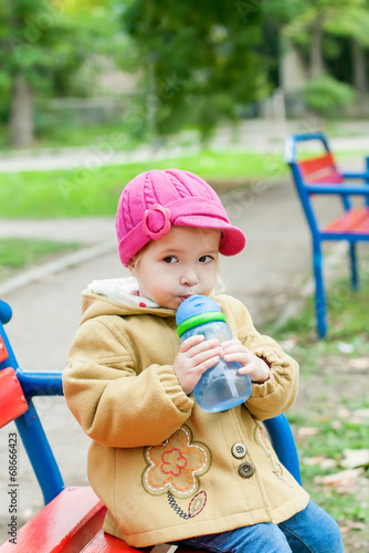 toddler girl sitting and drinks water - 68666423