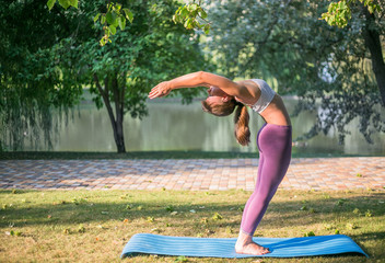 Young woman doing yoga in Park near lake