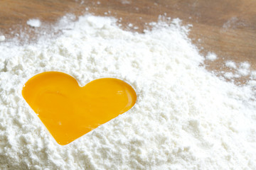 Yolk egg in flour love baking concept