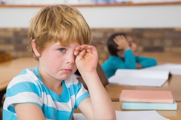 Upset pupil sitting at his desk
