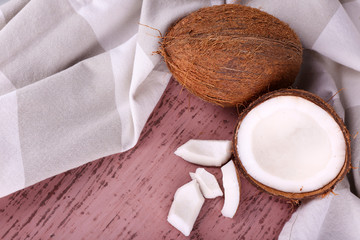 Broken coconut with napkin on wooden background