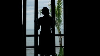 Woman unveil curtains, walking out on terrace with view at sea