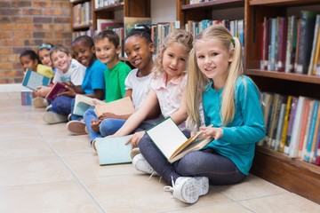 Cute pupils sitting on floor in library