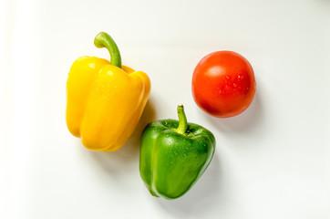 Paprika gelb gruen und Tomate nebeneinander auf weiss