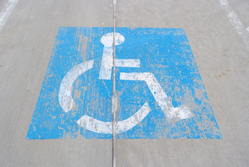 Old handicapped parking sign painted on concrete