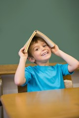 Happy pupil holding book on his head at desk