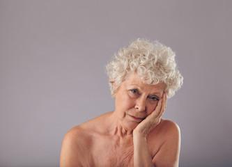 Upset senior woman on grey background