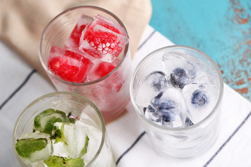 Ice cubes with mint leaves, raspberry and blueberry in glasses,