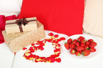 Romantic still life with strawberry, gifts and petals of roses