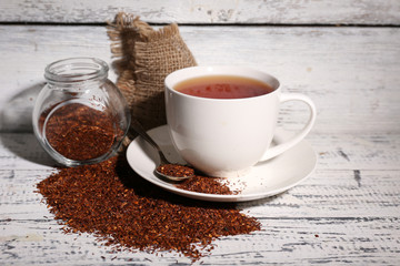 Cup of tasty rooibos tea, on old white wooden table
