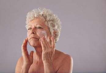 Mature caucasian woman applying anti-wrinkle face cream.
