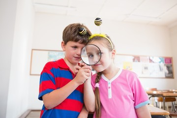 Cute pupils looking through magnifying glass