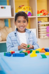 Cute little boy playing with building blocks