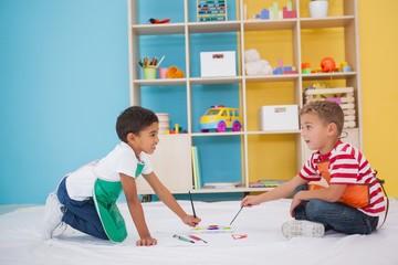 Cute little boys painting on floor in classroom