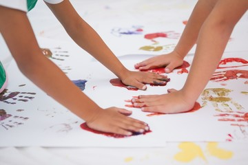 Cute little boys painting on floor in classroom
