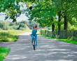 Woman with  bike in a country road.