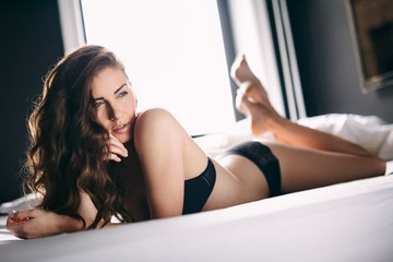 Young female in black lingerie lying on bed looking away