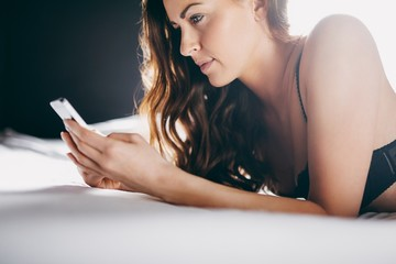 Beautiful young woman on bed texting with her cell phone