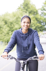 Portrait of smiling beautiful woman exercising with bicycle, out