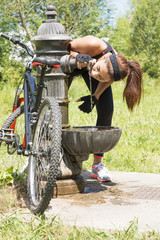 Athletic woman with bike drinking water after exercise, outdoor.