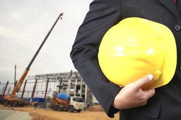 engineer holding yellow helmet for workers security on buildings