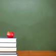 canvas print picture - Red apple on pile of books in classroom