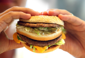 man's hands, holding onto a burger