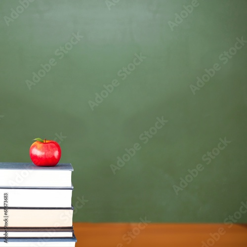 Red apple on pile of books in classroom