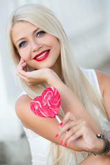 Elegant blonde with a lollipop in the shape of a heart