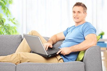 Young man siting at home on a sofa with laptop