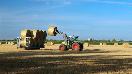 Traktor beim aufladen von Strohballen 16:9