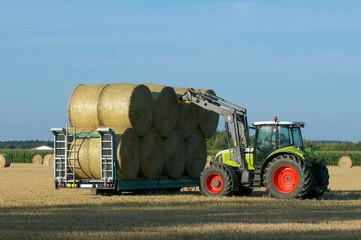 Traktor beim aufladen von Strohballen