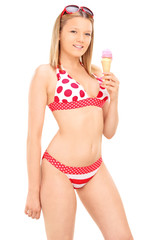 Vertical shot of a woman in bikini eating an ice cream