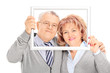 Mature couple posing behind a picture frame
