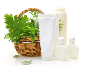 Fresh herbs in wicker basket and cosmetic packaging