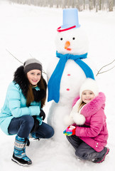 Smiling little girl and young woman with snowman in winter day