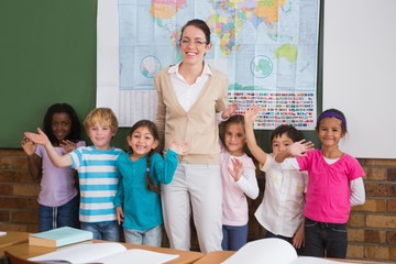 Teacher and pupils smiling at camera in classroom