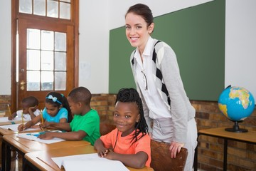 Cute pupil and teacher smiling at camera in classroom