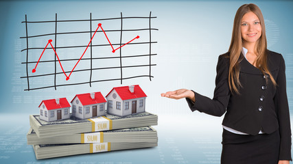 Businesswoman points hand on houses and money