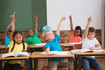 Cute pupils raising their hands